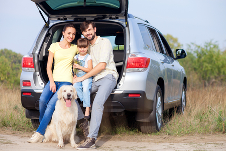 Pretty friendly family is making trip in the nature. They are sitting on car boot near dog and smiling. The man and woman are embracing their daughter. They are looking at camera with happiness