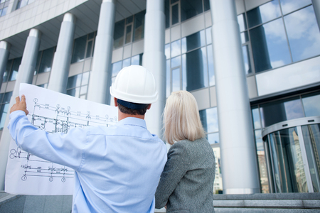 Skilful two architects are constructing new building. The man in helmet is holding blueprint. The businesswoman and worker are looking at sketches. They are standing outdoors Standard-Bild
