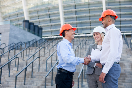 businessmen shaking hands: Professional engineers are shaking hands and smiling. The men are standing near building and looking at each other with trust. The woman is holding documents. Copy space in left side