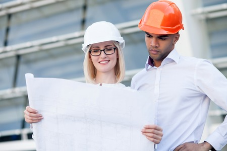blueprint: Attractive young engineers are discussing plan of building. The woman is holding blueprint and smiling. The man in helmet is looking at sketch with seriousness. They are standing near building