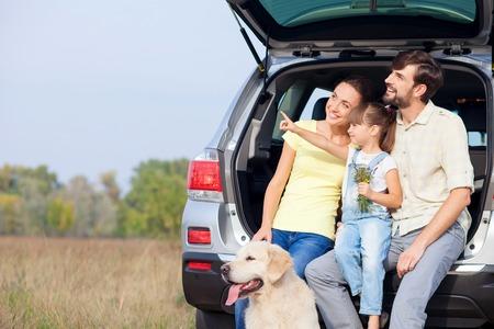 married: Alegre joven matrimonio y su hija están sentados en el tronco de coche cerca de perro. Están disfrutando de la naturaleza y sonriente. La muchacha está apuntando el dedo hacia los lados. Los padres están buscando allí con interés