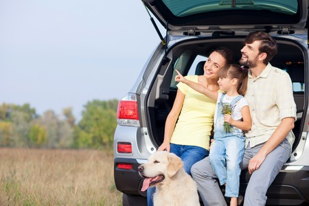 married: Cheerful young married couple and daughter are sitting on car trunk near dog. They are enjoying nature and smiling. The girl is pointing finger sideways. Parents are looking there with interest