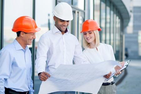Les ingénieurs prévoient la construction. Jeune homme tient plan. Ses collègues regardent croquis et souriant. La femme est en train d'écrire quelques notes Banque d'images