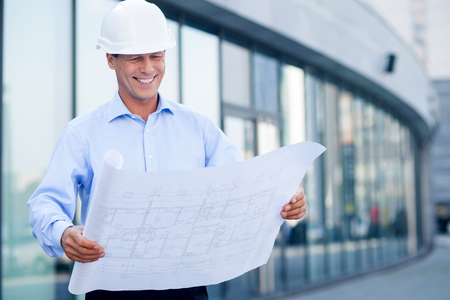 housing project: Professional architect is standing and holding blueprint. He is looking at sketch with inspiration and smiling. The man is wearing helmet. Copy space in right side