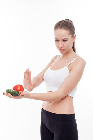 Attractive young woman is holding tomato and cucumber in her hands. He is gesturing and rejecting them. The lady is standing and looking vegetables with aversion. Isolated Stock Photo
