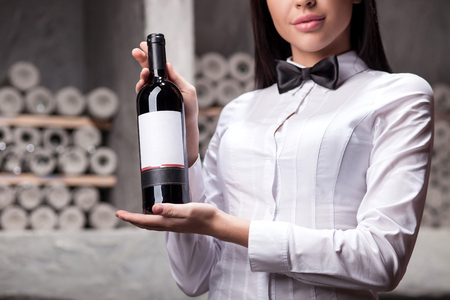 Close up of professional sommelier holding and showing a bottle of red wine. Stock Photo