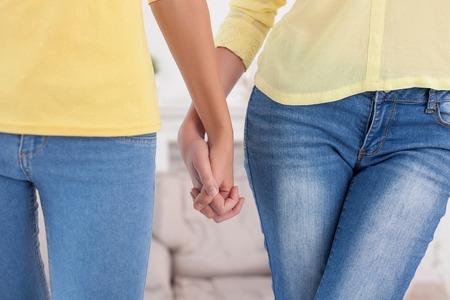 lesbianas: Primer plano de los brazos de pareja de lesbianas de pie y tomados de la mano Foto de archivo