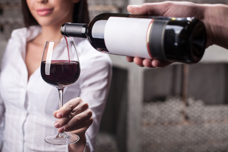 Close up of male hand of sommelier serving woman. The man is holding a bottle and pouring wine into glass. The woman is holding wineglass and smiling.