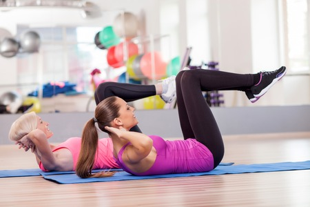 Cheerful young women are doing sit-ups in fitness center. They are lying and raising legs up