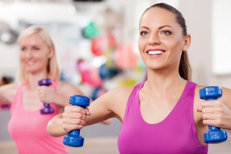 slim women: Cheerful slim women are exercising with weights in fitness center.