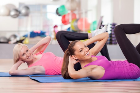 fun woman: Beautiful young slim women are doing exercise in gym. They are lying on carpers and stretching legs up Stock Photo