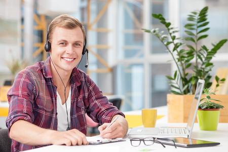 servicio al cliente: operador de sexo masculino joven hermoso está hablando por el manos libres. El hombre está sentado en el escritorio cerca de la computadora portátil y escribir notas