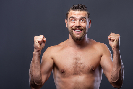 suave: Beautiful man is a fan of something. He is standing and holding fists with anxiety. The man is smiling and looking forward with hope. Isolated on grey background Stock Photo