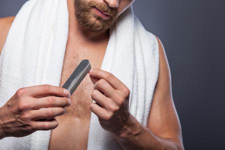 hombres jovenes: Cierre para arriba del hombre joven pulir las u�as con bien. �l est� de pie con una toalla blanca. Aislado