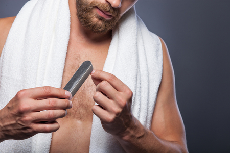 nail file: Close up of young man polishing his nails with fine. He is standing with white towel. Isolated Stock Photo