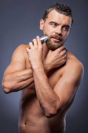 pensiveness: Cheerful young man is standing and shaving his beard. He is holding electric razor. The man is looking forward with pensiveness and doubt. Isolated on grey background Archivio Fotografico