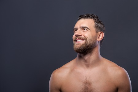 suave: Attractive young bearded man is standing and posing. The man is looking up and smiling. Isolated on grey background and copy space of left side
