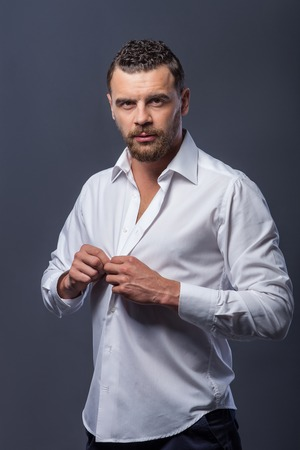 men standing: Handsome young bearded man is standing and looking at camera with passion. He is wearing white shirt and buttoning up it. Isolated on grey background Stock Photo