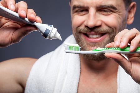 dientes: Cerca de la atractiva hombre barbudo joven es cepillarse los dientes. Él está de pie y sonriente. El hombre está apretando pasta de dientes en el cepillo de dientes. Centrarse en herramientas de limpieza