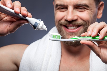 teeth cleaning: Close up of attractive young bearded man is brushing his teeth. He is standing and smiling. The man is squeezing tooth-paste into tooth-brush. Focus on cleaning tools