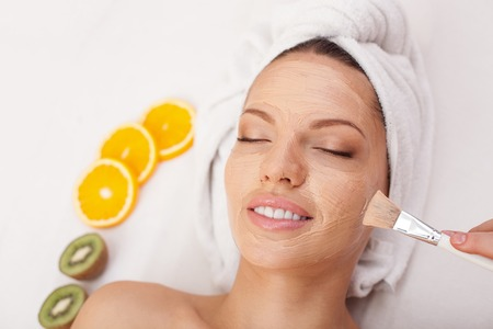 Attractive young woman is having facial clay mask at spa. The beautician is applying cream on female face carefully Фото со стока