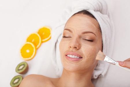 pulizia viso: Attraente giovane donna sta avendo maschera di argilla viso a spa. L'estetista � applicare la crema sul volto femminile con attenzione Archivio Fotografico