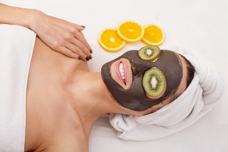 facial: Beautiful young woman is getting facial chocolate mask at spa. The lady has pieces of kiwi on her eyes and white towel over head.
