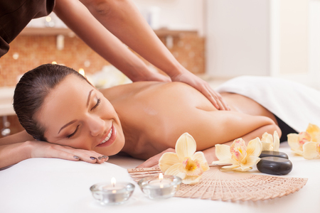 massage: Gros plan des mains de masseuse massage dos de jeune femme. La belle femme est couchée et relaxant. Banque d'images