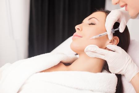 Gros plan des mains de jeunes cosmétologue injection botox dans le visage féminin.