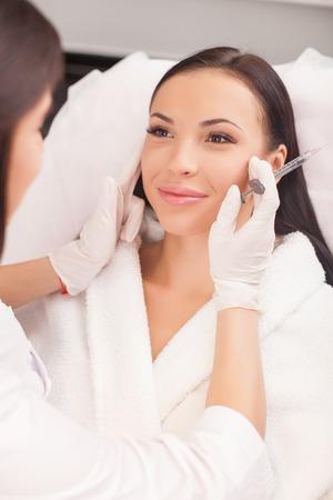 inyeccion: Joven y bella mujer está recibiendo la inyección de botox en la cara. La doctora está comprobando su piel con la concentración y la celebración de una jeringa