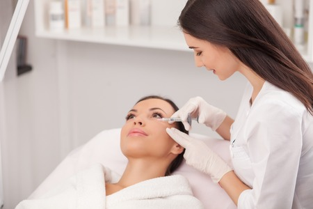 Attractive young woman is getting a collage injection in her face. The expert beautician is filling female nasolabial wrinkles by hyaluronic acid and smiling