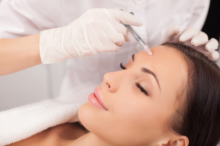 injection woman: Close up of hands of expert beautician injecting botox in female forehead. Stock Photo