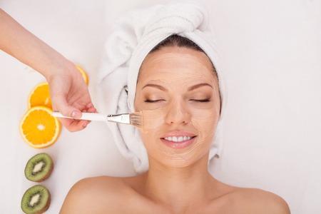 Close-up van de handen van de schoonheidsspecialiste toepassing klei cosmetische masker op vrouwelijk gezicht Stockfoto