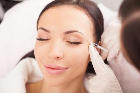 Aantrekkelijke gezonde vrouw krijgt botox injectie en glimlachen. De deskundige schoonheidsspecialist vult hyaluronzuur in het vrouwelijke gezicht met een spuit