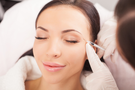 Attractive healthy woman is getting botox injection and smiling. The expert beautician is filling hyaluronic acid into female face with syringe