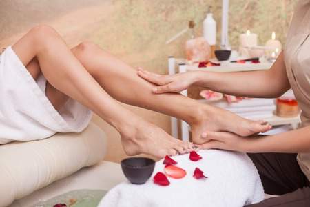 Close up of hands of masseuse massaging female legs at spa. The woman is sitting near small bath with petals Stock Photo