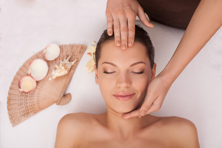 masseuse: Close up of arms of masseuse massaging female forehead and chin. Stock Photo