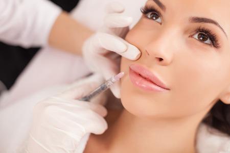 美容: 特寫美容師的做肉毒桿菌注射在女性的嘴唇手。這位年輕漂亮的女子正在接受與享受過程 版權商用圖片