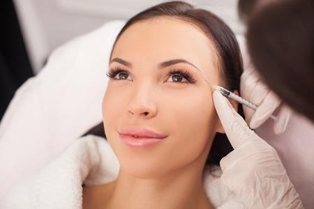 美しい若い女性は、クリニックでボトックス注射を取得です。医師は慎重に彼女の眉毛近くシリンジを保持しています。