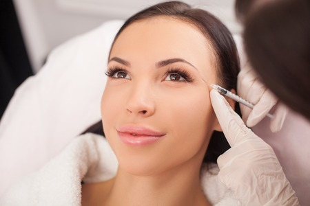 botox: Beautiful young woman is getting botox injection at clinic. The doctor is holding syringe near her eyebrows carefully