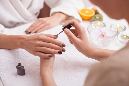 manicure: Close up of arms of young woman getting manicure at spa.