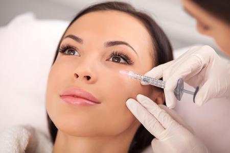 美しい若い女性は、彼女の顔に噴射をなっています。医師は慎重にシリンジを保持していると立っています。