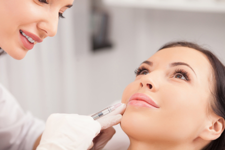 Cheerful young woman is getting botox procedure. The doctor is standing near her and smiling. She is holding syringe and touching it to female face Standard-Bild