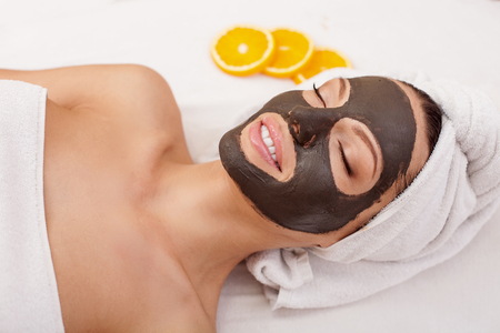 Beautiful young woman is getting facial chocolate mask at spa