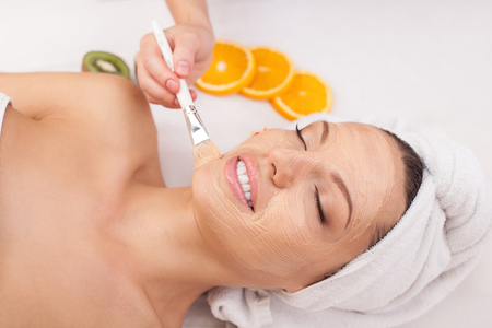 Beautiful young woman is getting facial cosmetic mask at spa. She is lying and relaxing. The lady is smiling with closed eyes. The beautician is applying cream on her face with brush