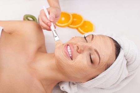 pulizia viso: La bella giovane donna sta ottenendo facciale maschera cosmetica a spa. Lei � sdraiata e rilassante. La signora sorride con gli occhi chiusi. L'estetista sta applicando la crema sul viso con il pennello Archivio Fotografico