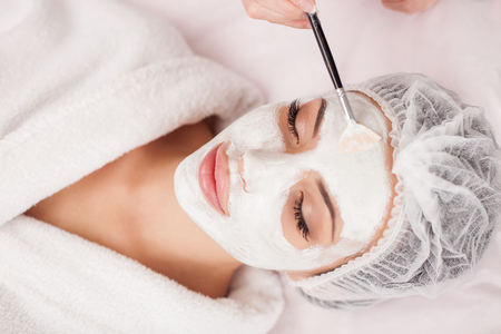 Beautiful young woman is getting facial mask at spa. She is lying and relaxing. Her eyes are closed with pleasure. The cosmetologist is applying cream on her face with brush Reklamní fotografie - 46914865