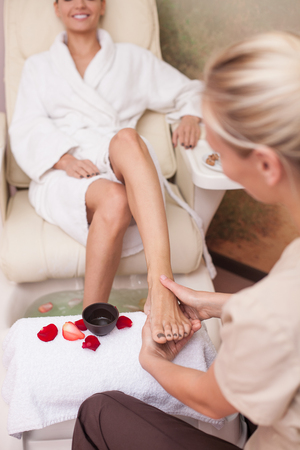Professional young masseuse is massaging foot of her client with concentration