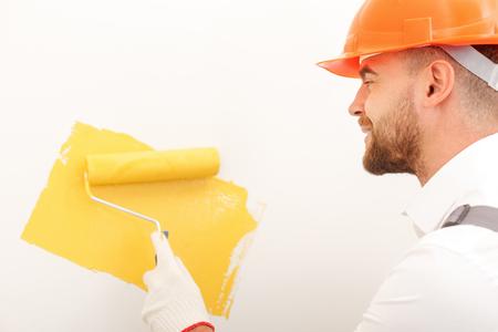 albañil: constructor joven alegre es pintura de pared con el color amarillo. Él está de pie y sonriente. El hombre es la celebración de un rodillo