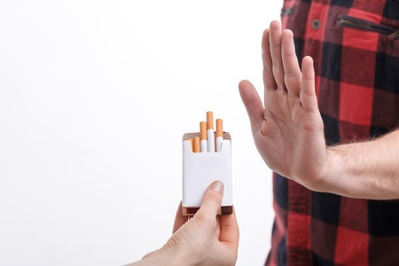refusing: Close up of male hand refusing to smoke. The human hand is holding a pack of cigarettes and proposing it to man. Isolated and copy space in left side